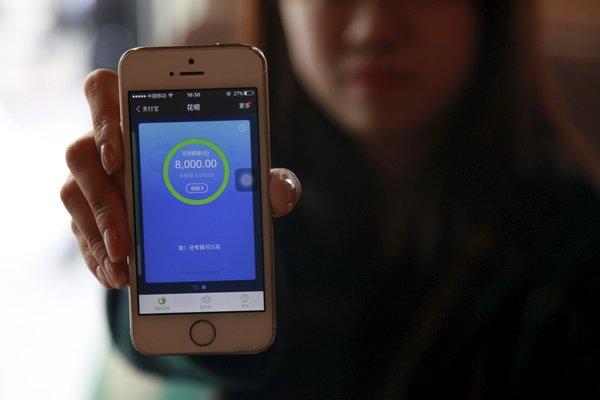 铁路检票员庞宇(音)展示自己手机上的蚂蚁花呗。这是阿里巴巴旗下的在线支付公司蚂蚁金服推出的一项服务。