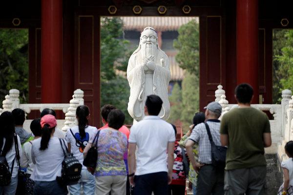 在位于北京的孔庙里,游客和学生站在古代哲学家孔子的雕塑前。他的学说还在持续影响着中国社会。